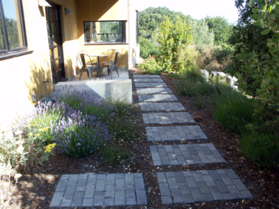 stepping stones made for interlocking pavers lead to side patio