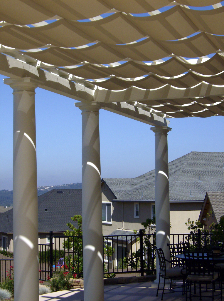 White stately pillars with canvas sails for shade.