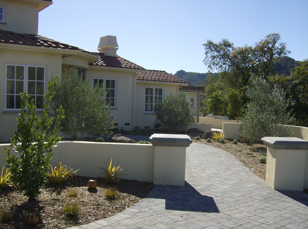Entry from paver driveway into front yard with stucco columns