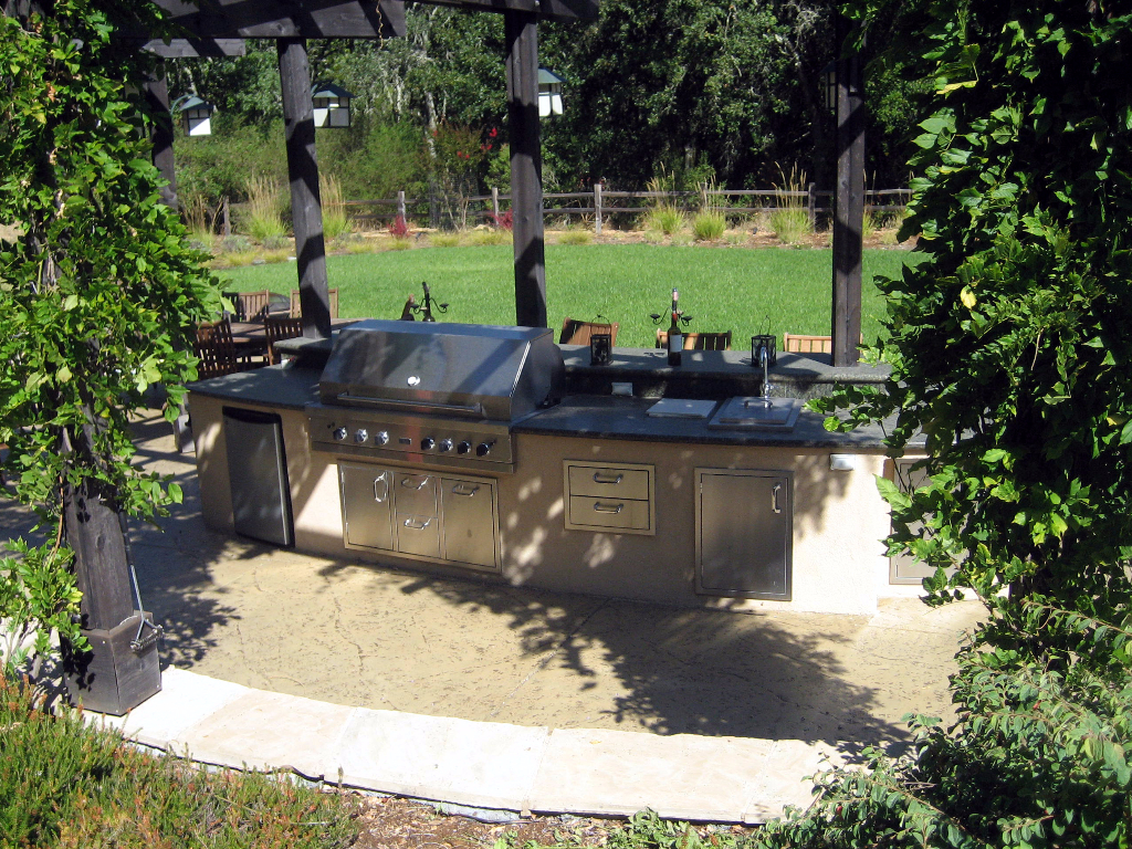 Outdoor kitchen with many drawers and cabinets under pergola