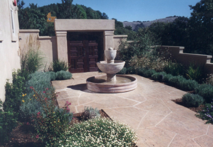 Double doors in stucco wall with fountain at entry patio