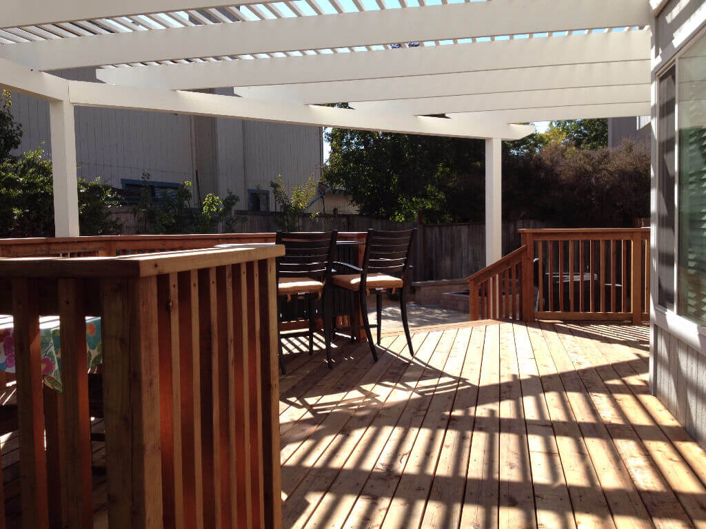 Wooden deck provides outdoor living space while casting shade and allowing light.
